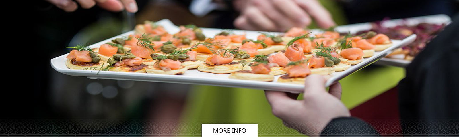 Salmon and capers horderves on a serving tray held by a waiter
